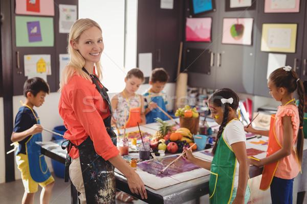Portrait of smiling teacher assisting schoolkids in drawing class Stock photo © wavebreak_media