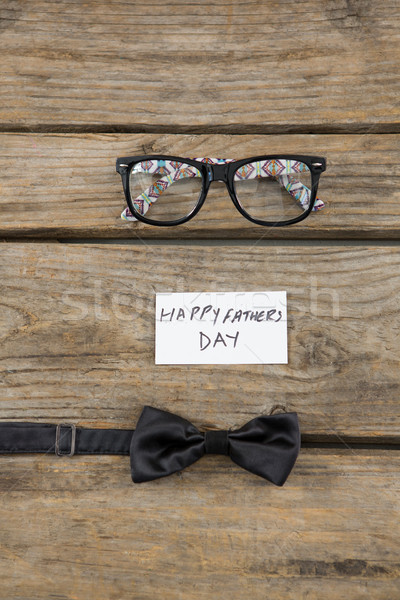 Happy fathers day text by eyeglasses and  bow tie on table Stock photo © wavebreak_media