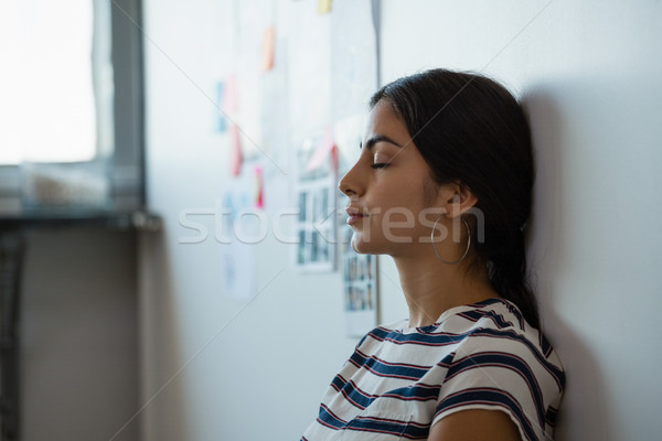 Tired woman leaning on wall in office Stock photo © wavebreak_media