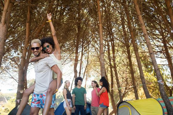 Happy man piggybacking woman with friends in background Stock photo © wavebreak_media