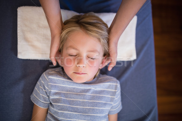 Overhead view of boy with eyes closed receiving neck massage from female therapist Stock photo © wavebreak_media