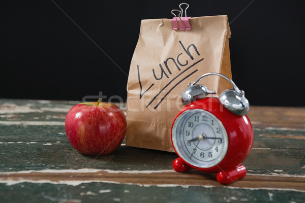Apple, alarm clock and lunch bag on wooden table Stock photo © wavebreak_media