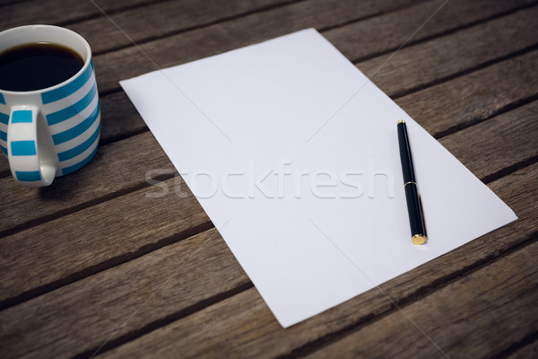 Paper and fountain by coffee cup on wooden table Stock photo © wavebreak_media