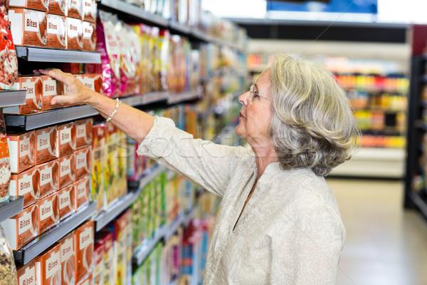 Senior woman picking food from aisle Stock photo © wavebreak_media