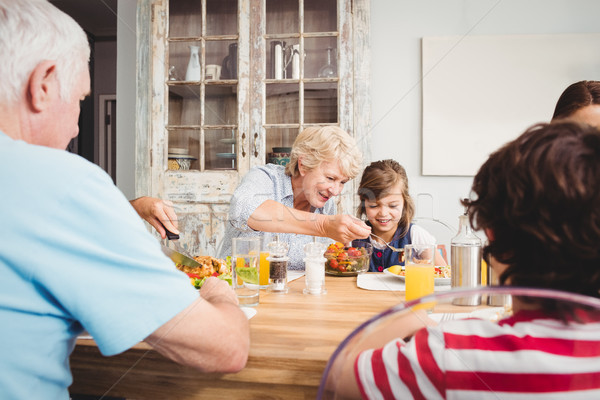 Smiling granny and granddaughter while sitting at dining table Stock photo © wavebreak_media
