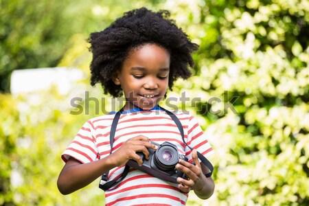 Little girl lying on floor holding camera in her hand on a sunny day Stock photo © wavebreak_media