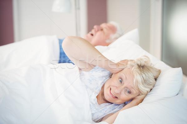 Senior woman blocking ears while man snoring on bed Stock photo © wavebreak_media