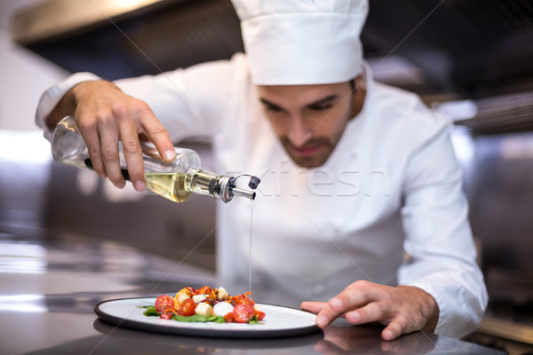 Handsome chef pouring olive oil on meal Stock photo © wavebreak_media