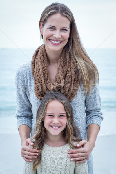 Happy mother standing with daughter at sea shore Stock photo © wavebreak_media