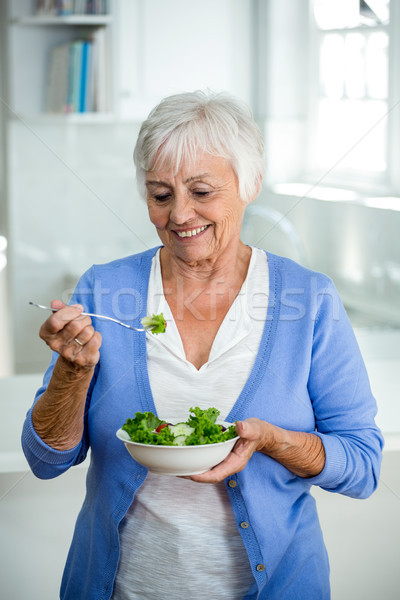 Senior woman eating salad while standing in kitchen Stock photo © wavebreak_media