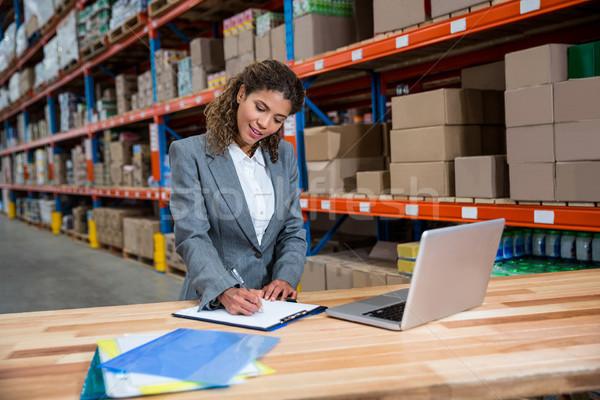 Femme d'affaires écrit presse-papiers entrepôt ordinateur bureau Photo stock © wavebreak_media