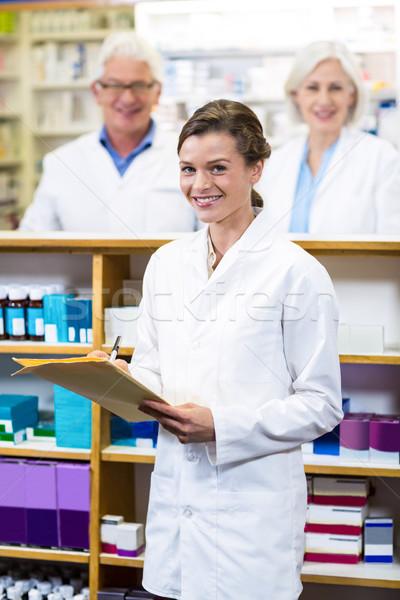 Pharmacist writing on file in pharmacy Stock photo © wavebreak_media