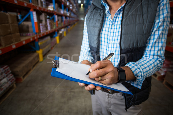 Stock photo: Mid section of warehouse worker writing on clipboard