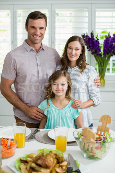 Portrait of smiling family having lunch together on dining table Stock photo © wavebreak_media