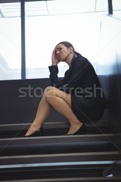 Depressed businesswoman with hand on her head sitting on stairs Stock photo © wavebreak_media