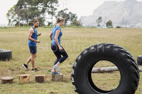 Fit woman running on wooden logs while trainer measuring time Stock photo © wavebreak_media