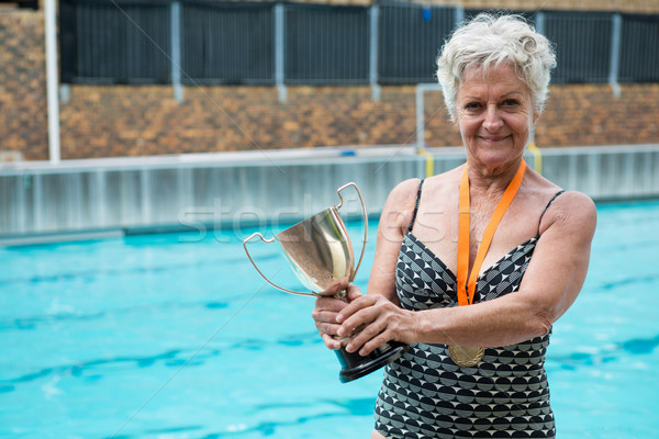 Senior woman holding trophy at poolside Stock photo © wavebreak_media
