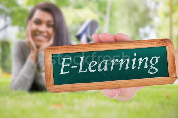 E-learning against pretty brunette smiling at camera in park Stock photo © wavebreak_media