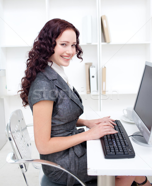 Stock photo: Smiling businesswoman working in office with a computer