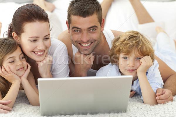 Parents enfants lit utilisant un ordinateur portable fille fils Photo stock © wavebreak_media