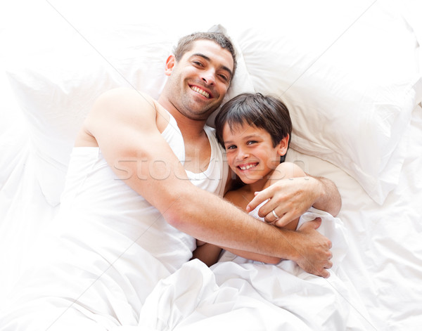 Happy father and his son looking at the camera on the bed Stock photo © wavebreak_media