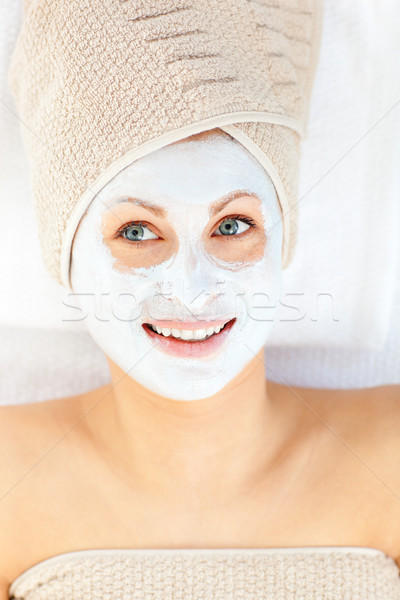 Radiant young woman having white cream on her face lying in a spa center Stock photo © wavebreak_media
