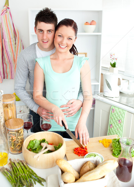 Enamored young couple cutting vegetables in the kitchen at home Stock photo © wavebreak_media