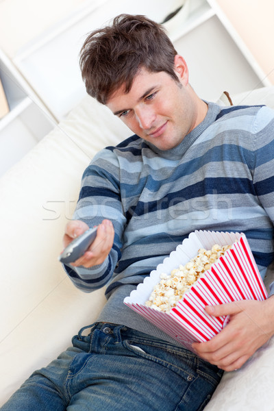 Elragadtatott fiatalember eszik pattogatott kukorica tart távoli Stock fotó © wavebreak_media