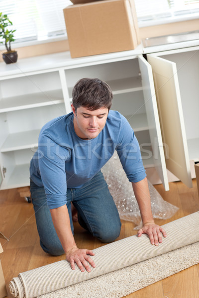 Handsome man rolling a carpet out in his new house Stock photo © wavebreak_media