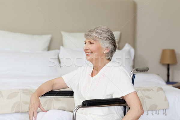 Stock photo: Smiling senior woman in her wheelchair