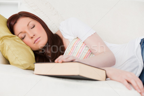 Beautiful red-haired girl having a rest while studying on a sofa in the living room Stock photo © wavebreak_media