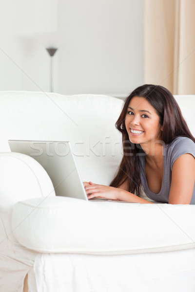 charming woman lying on sofa with notebook looking into camera in livingroom Stock photo © wavebreak_media