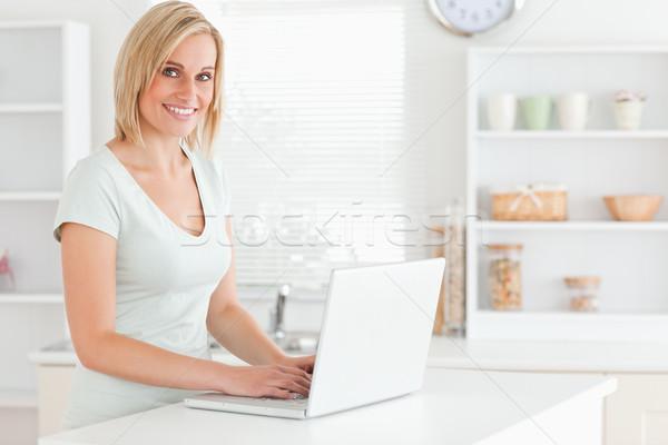 Bájos nő laptop néz kamera konyha Stock fotó © wavebreak_media