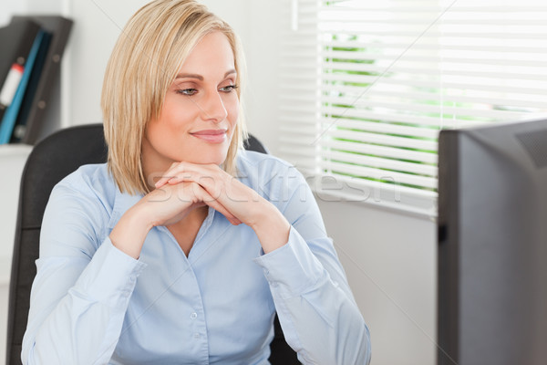 Cute blonde woman with chin on her hands behind a desk looking at screen in office Stock photo © wavebreak_media