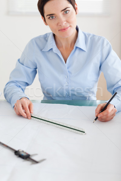 Gorgeous Woman working on an architectural plan looking into the camera in an office Stock photo © wavebreak_media