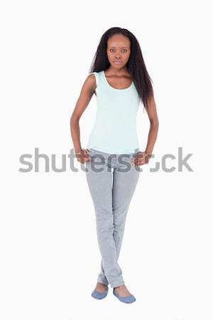 Genç kadın ayakta bacak bacak beyaz arka plan imzalamak Stok fotoğraf © wavebreak_media