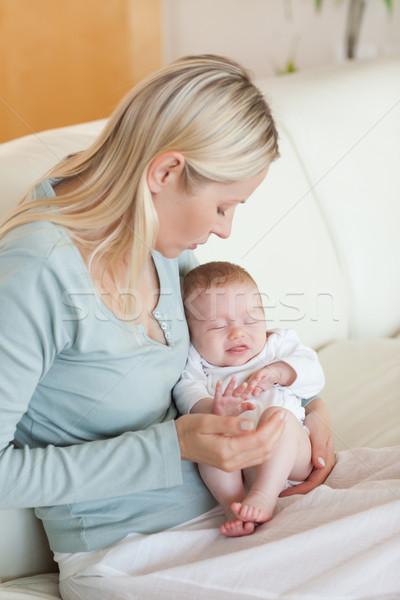 Young mother on the sofa with her baby on her lap Stock photo © wavebreak_media