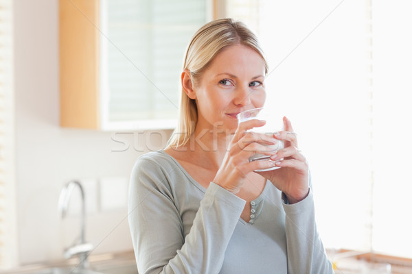 Young woman standing in the kitchen drinking some water Stock photo © wavebreak_media