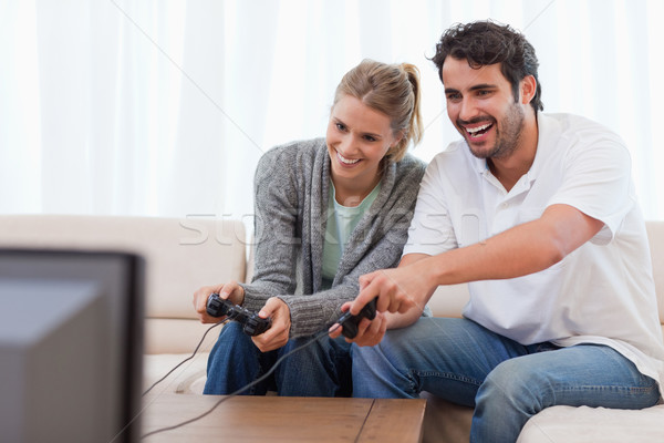 Stock photo: Couple playing video games in their living room