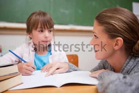 Cute schoolgirl writing a while her teacher is talking in a classroom Stock photo © wavebreak_media