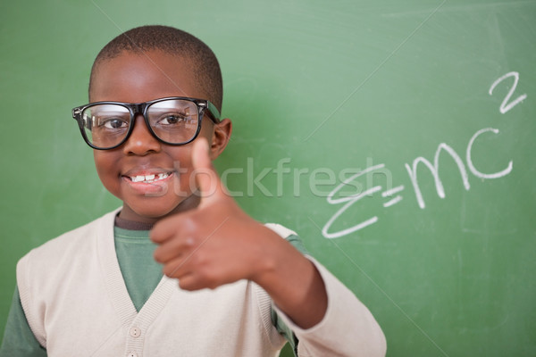 Schoolboy posing with the the mass-energy equivalence formula and the thumb up in front of a blackbo Stock photo © wavebreak_media