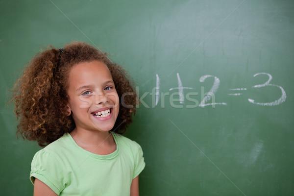Schoolgirl posing in front of an addition on a blackboard Stock photo © wavebreak_media