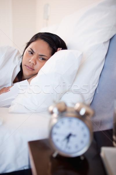 Vista lateral mulher jovem irritado despertador cama quarto Foto stock © wavebreak_media