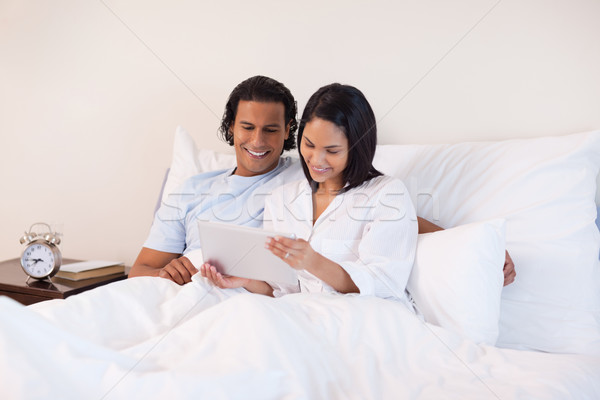 Young couple surfing the internet on the bed Stock photo © wavebreak_media
