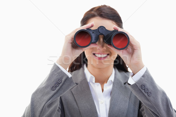 Close-up of a businesswoman smiling and looking through binoculars against white background Stock photo © wavebreak_media