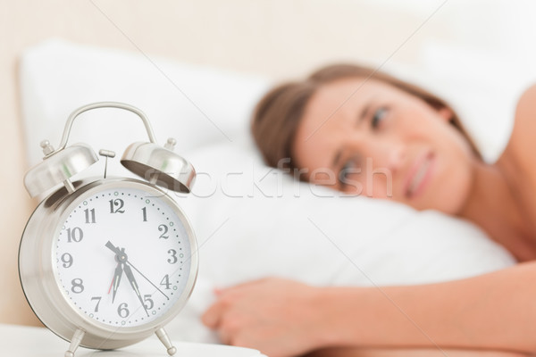 A woman in bed awake with her alarm clock on the desk beside her. Stock photo © wavebreak_media