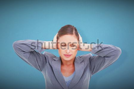 Close up of irritated tradeswoman covering her ears against a white background Stock photo © wavebreak_media