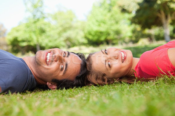 Two friends smiling while looking towards the side as they lie head to head on the grass Stock photo © wavebreak_media