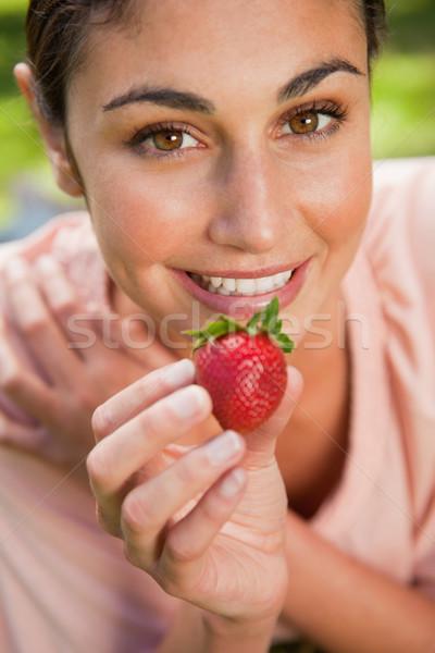 Mulher sorrindo oferta morango mentiras grama cara Foto stock © wavebreak_media