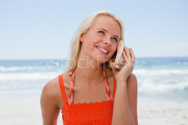 Young blonde woman listening to the sound of the sea through a shell Stock photo © wavebreak_media